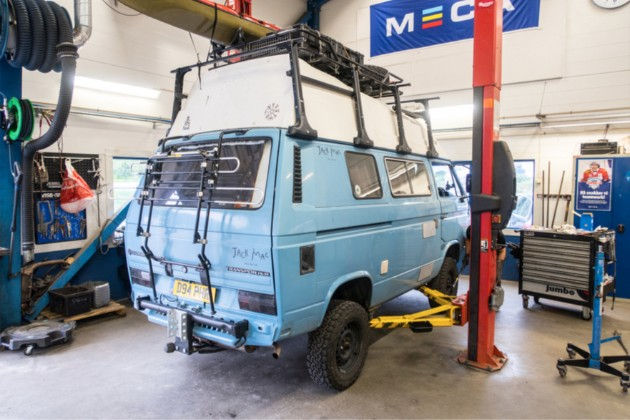 Right angled view of a light blue VW van on a car lift in a auto repair shop