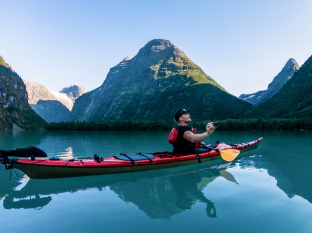 A person in a red kayak on a rippleless lake in the mountains