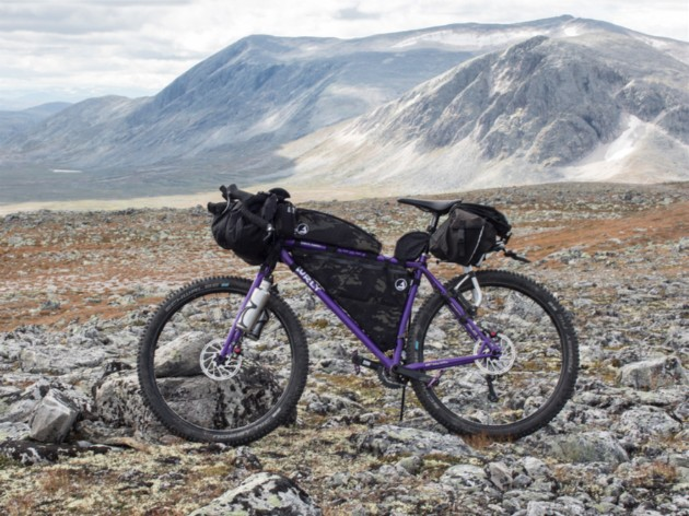 Left side view of a purple Surly bike loaded with gear standing a rocky field in the mountains