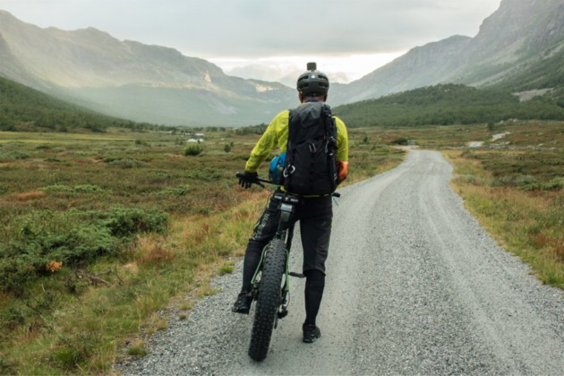 Cyclist facing down a gravel road in the mountains on a fat bike loaded with gear