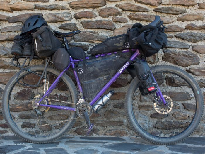 Ride side view of a custom Surly Karate Monkey bike loaded with gear leaning  on a stone wall