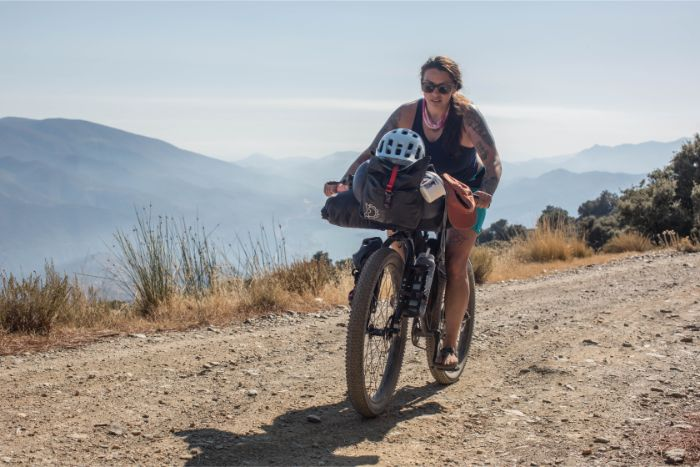 Cyclist rides up a gravel road in the mountains