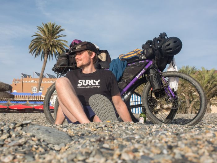 Jack Mac sits with a Surly bike loaded with gear on a gravel beach with palm trees behind