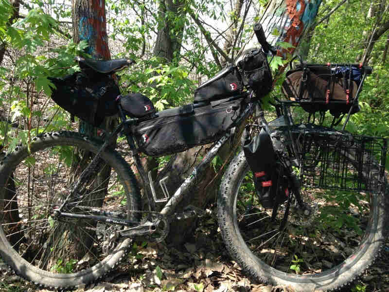 Right side view of a dirty, black Surly Karate Monkey bike loaded with gear, parked against a tree in the woods