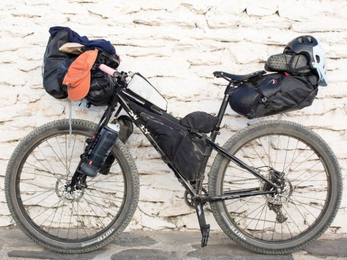 Left side view of a Surly bike loaded with gear leaning against a stone wall