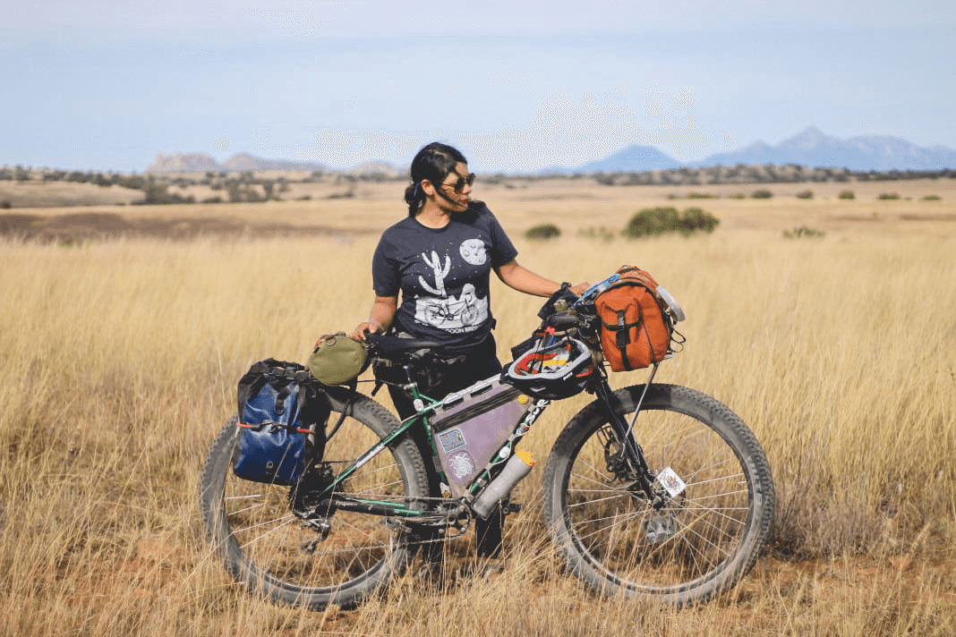 Side view of a Cyclist standing with a fat bike loaded with gear in a brushy field with mountain behind in the distance