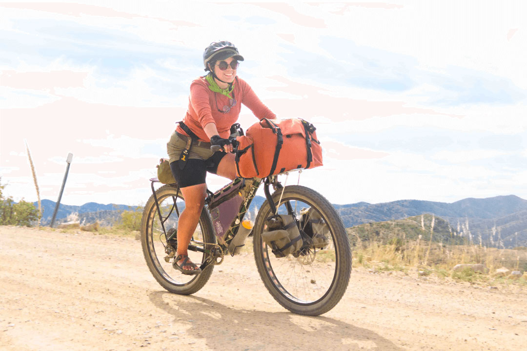 Cyclist smiling rides a fat bike loaded with gear rides on a gravel road down a hill with mountains in the distance