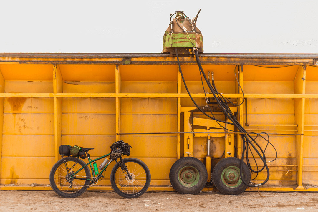Right side view of a green Surly fat bike loaded with gear leaning on a large yellow steel container with two wheels
