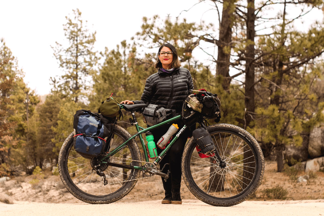 Cyclist stands with a Surly fat bike, green, loaded with gear on a gravel road with trees in the background