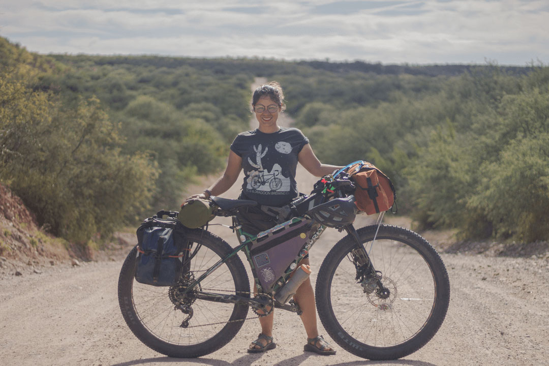 Cyclist on a fat bike with gear looks up a hill from a desert gravel road with large cactuses and hills in background
