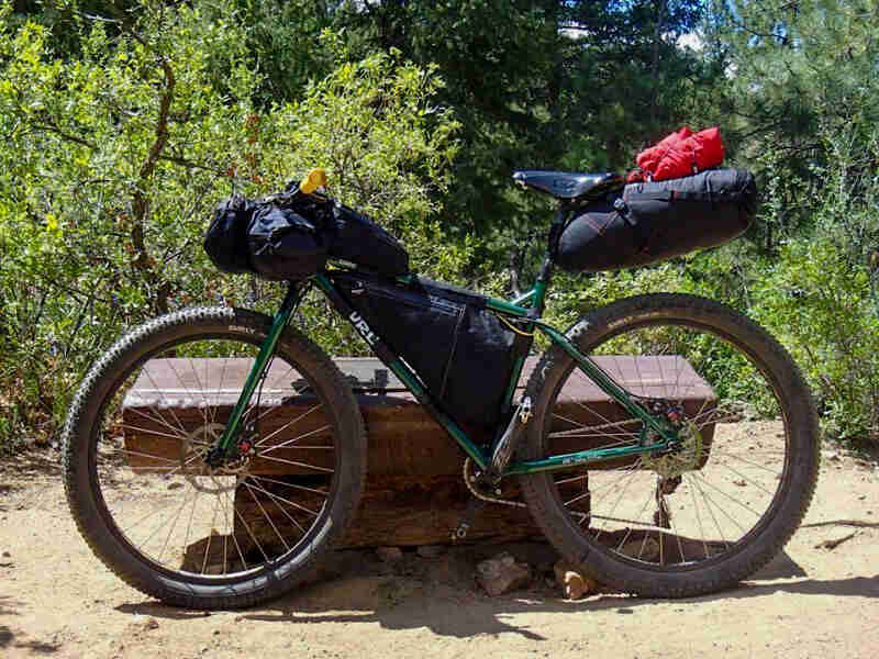 Left profile of a Surly Krampus bike, green, loaded with gear, in front of a bench, with the forest in the background