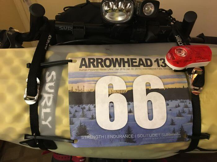 Bike handlebar pack with a light and Arrowhead 135 banner