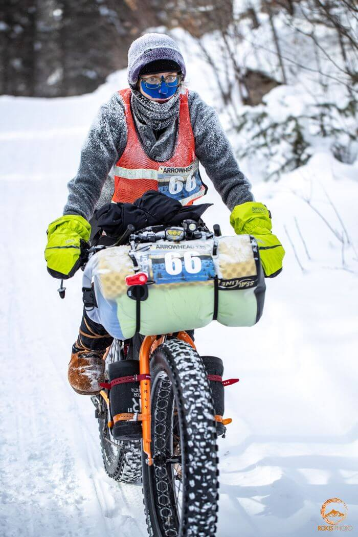 Cyclist wearing winter clothing rides an orange Surly fat bike on a snowy trail in the woods