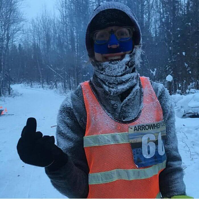 Person wearing winter clothing smiles and sticks up a gloved middle finger on a snowy day in the woods