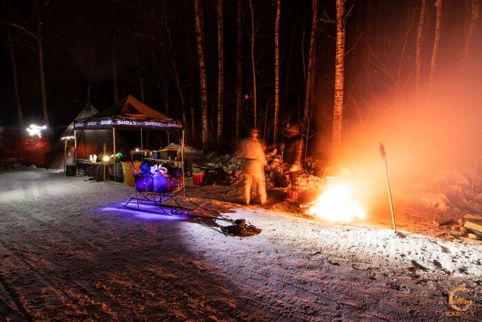 A campsite at night with a campfire and and a pop up canopy in the snowy woods
