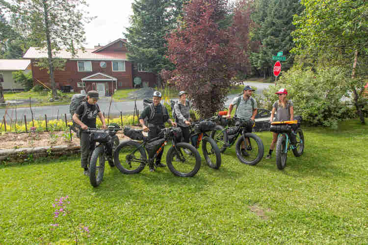 A group of cyclists with their fat bikes loaded with gear, stand on the grass in a front yard