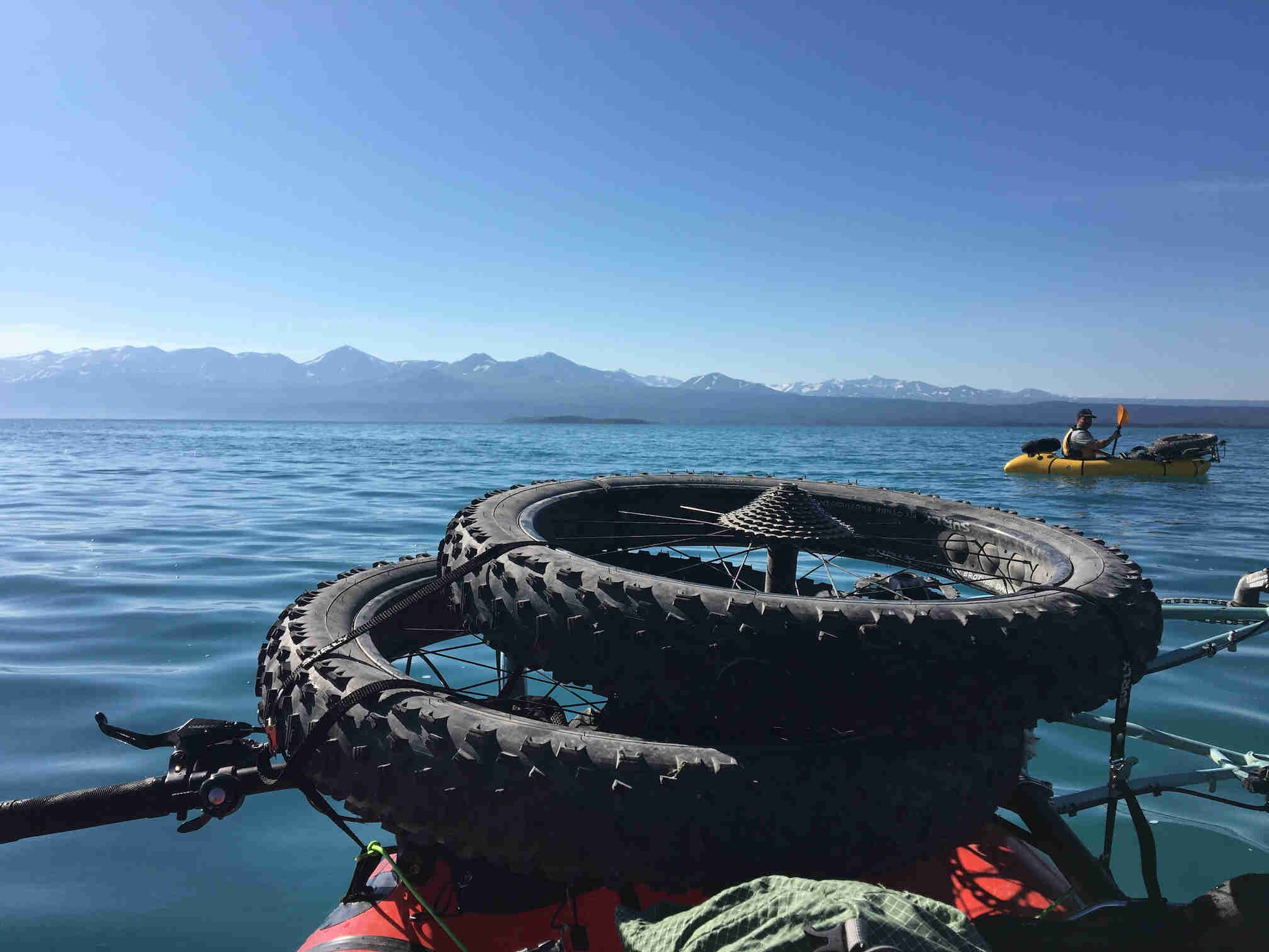 Close up of fat bike wheels on the front of a kayak on a lake, with mountains in the background