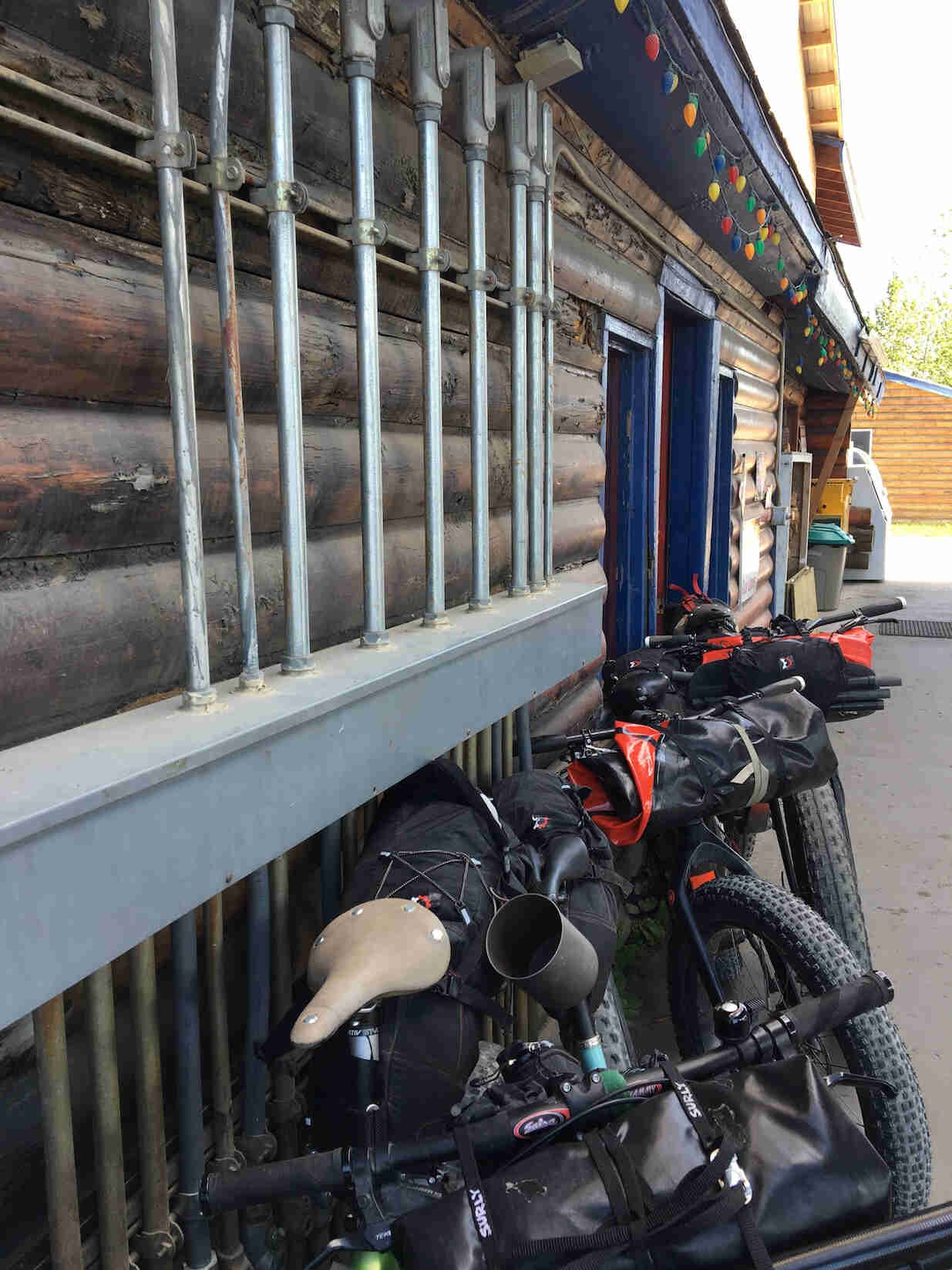 Side view of fat bikes lined up against the wall outside of a log building