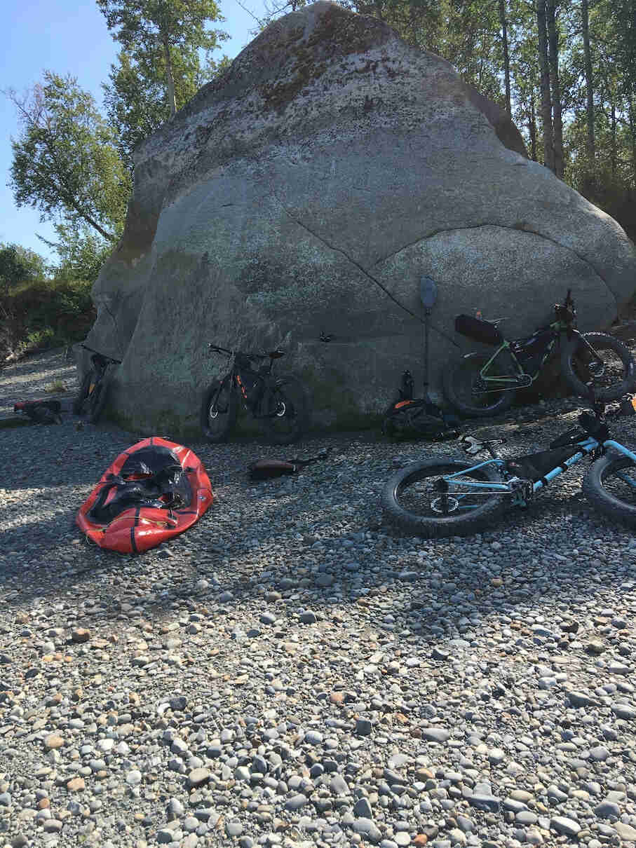 Fat bikes leaning on and around a large boulder on a rocky beach, with tree in the background