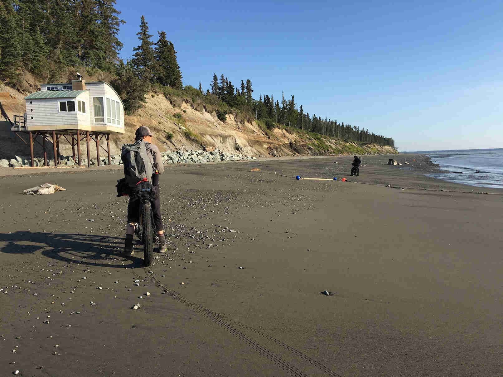 Rear view of a cyclist standing with their fat bike on a beach with water to the right, a building on stilts