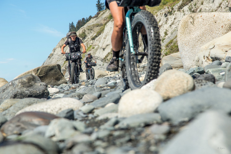 Front view of cyclists riding their fat bikes down a rocky shore, with a rock cliff in the background