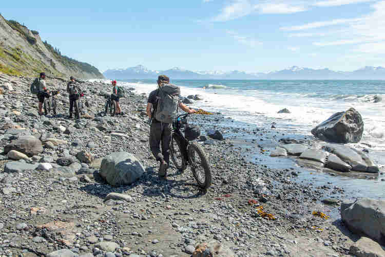 Rear view of a cyclist walking with a fat bike on a rocky shore towards 3 friends, with mountains in the background