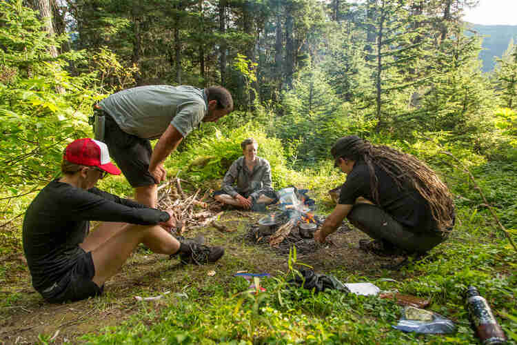 Four people sitting around a campfire on a grass clearing on a mountain hill, with trees in the background