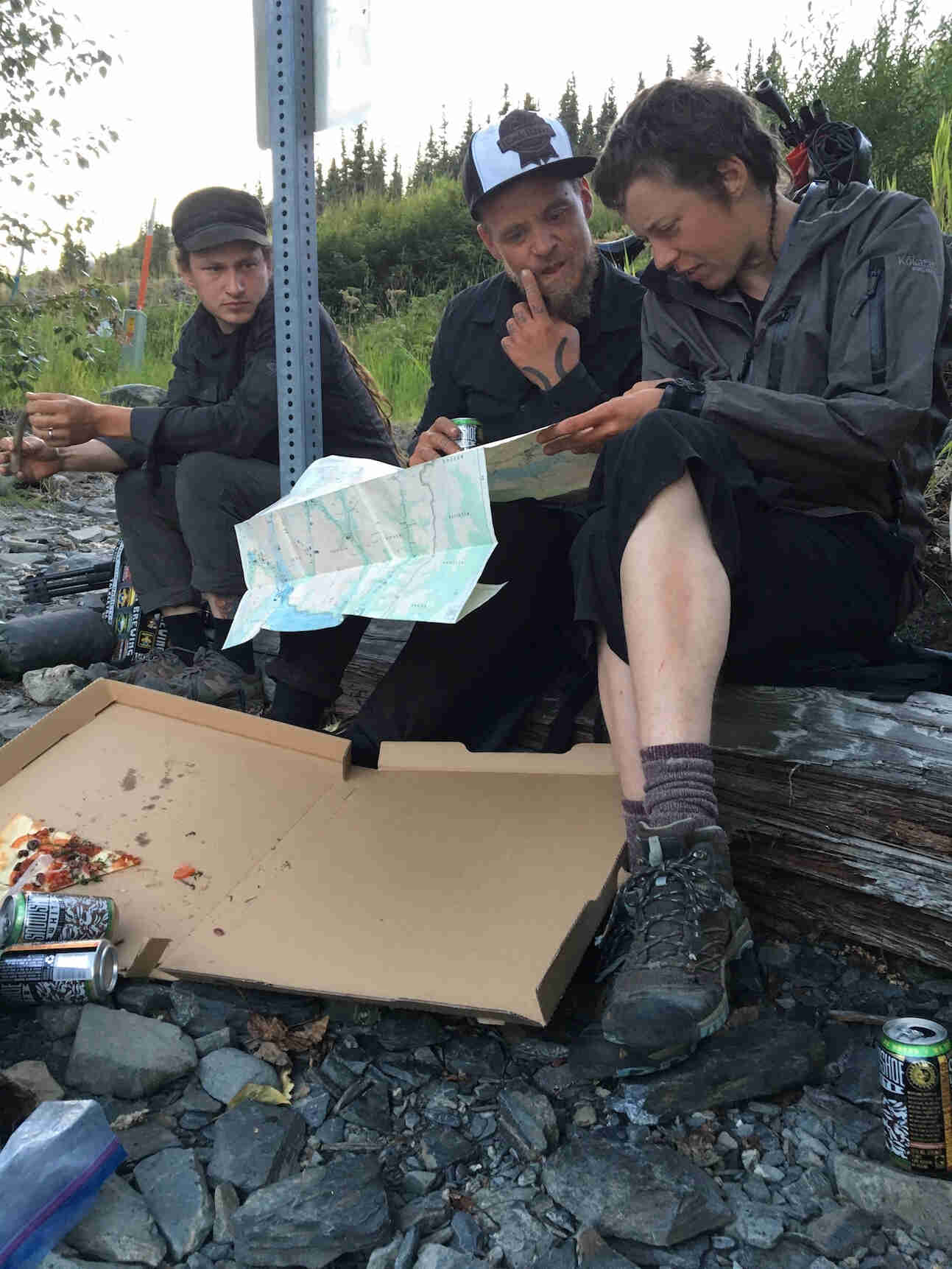 Front view of 3 people sitting on a log, looking at a map, with a pizza box sitting on the ground in front of them