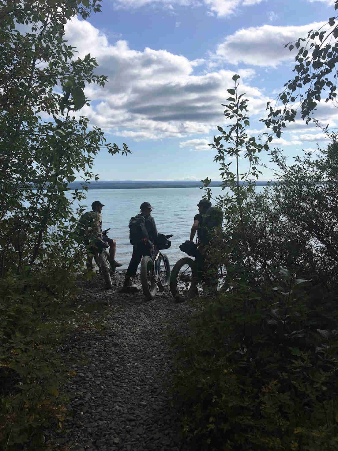 Rear view of three cyclists standing with their fat bikes, at the end of a gravel trail, in front of a lake