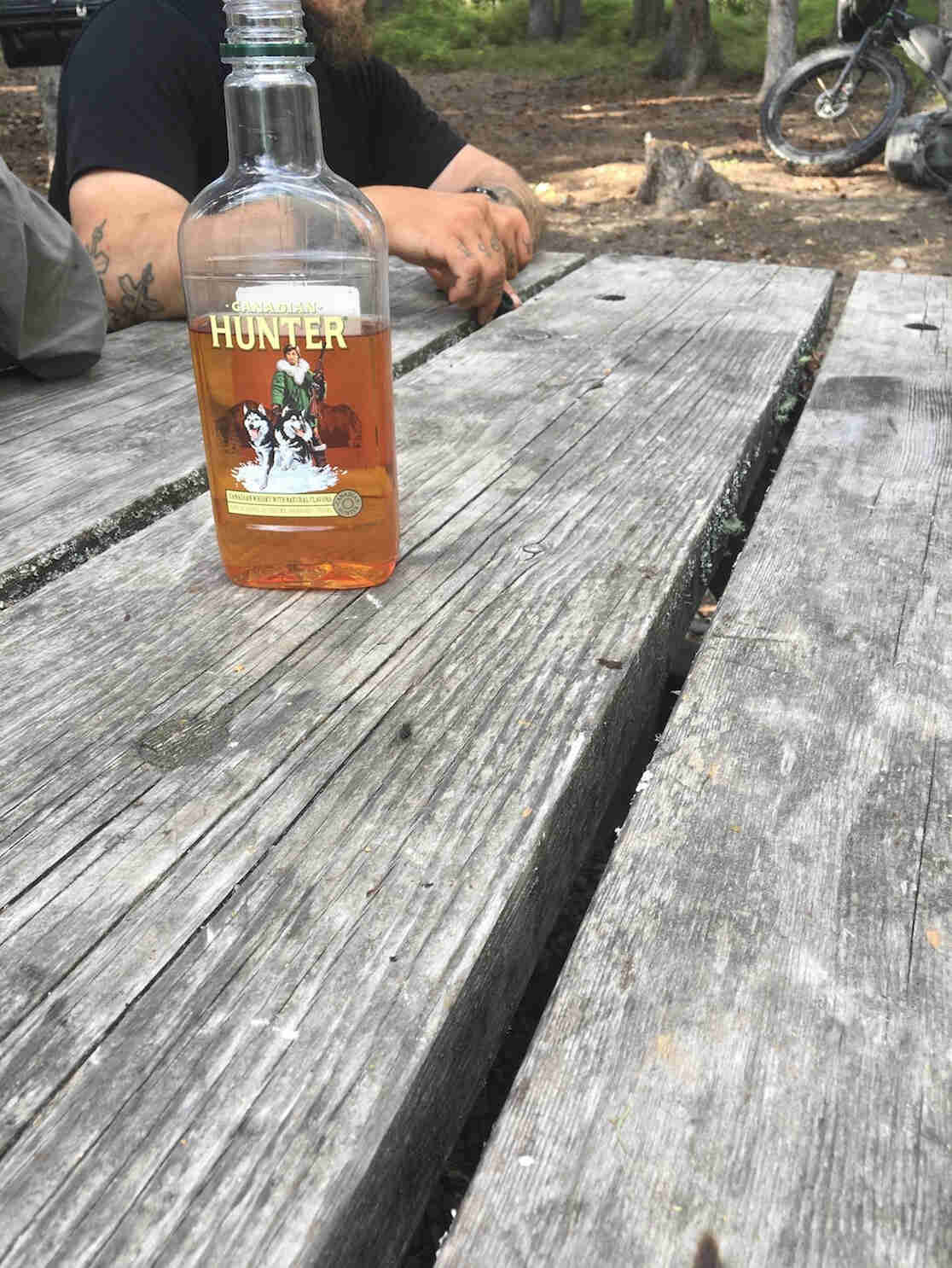 A bottle of Hunter liquors, on a picnic table, with a person sitting at the left end
