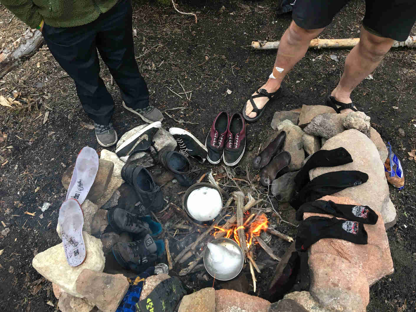 Downward view of shoes and socks on the rocks around a campfire