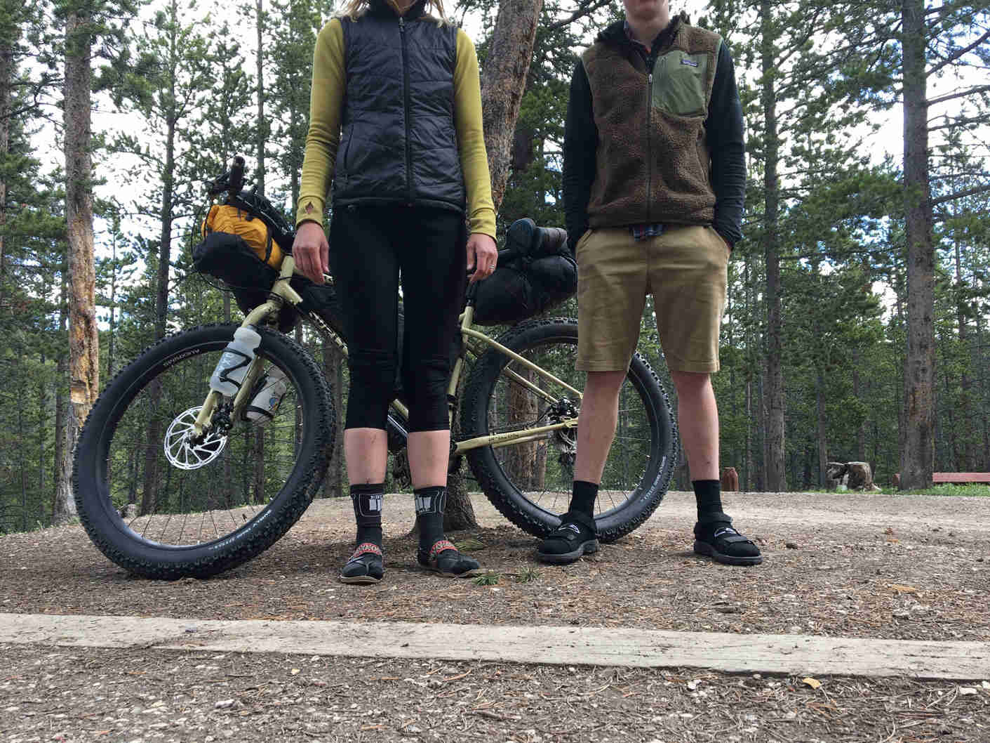 Two cyclists standing in front of a Surly ECR bike, on gravel, with pines trees in the background