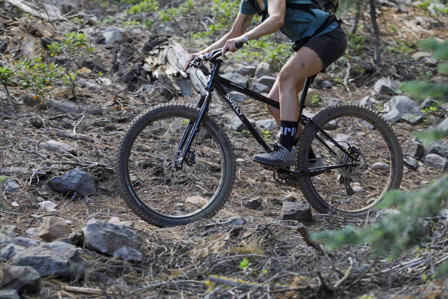 Left side view of a cyclist on a Surly Karate Monkey bike, black, across a rocky hill in the forest