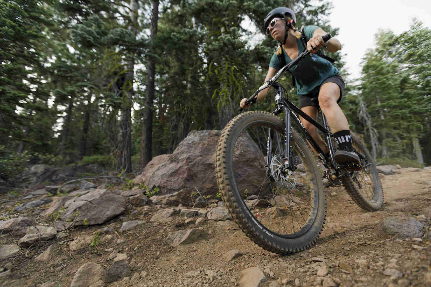 Front left view of a cyclist on a Surly Karate Monkey bike, black, riding down a rocky dirt trail in the forest