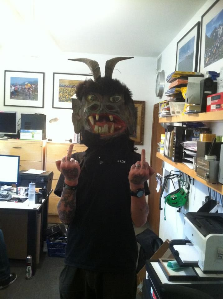 Front view of a person, wearing a Krampus costume head, holding up their middle fingers, in an office