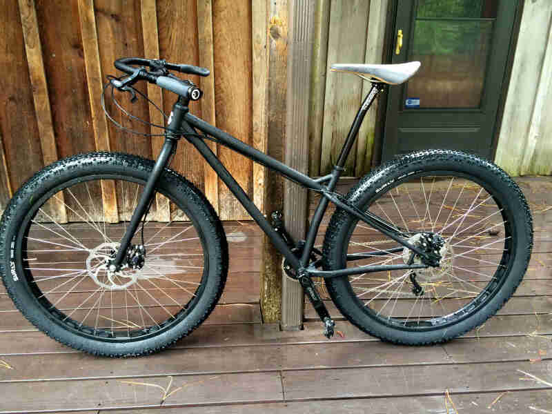 Left side view of a Surly Krampus bike, matte black, in front of a wood sided wall, on a porch