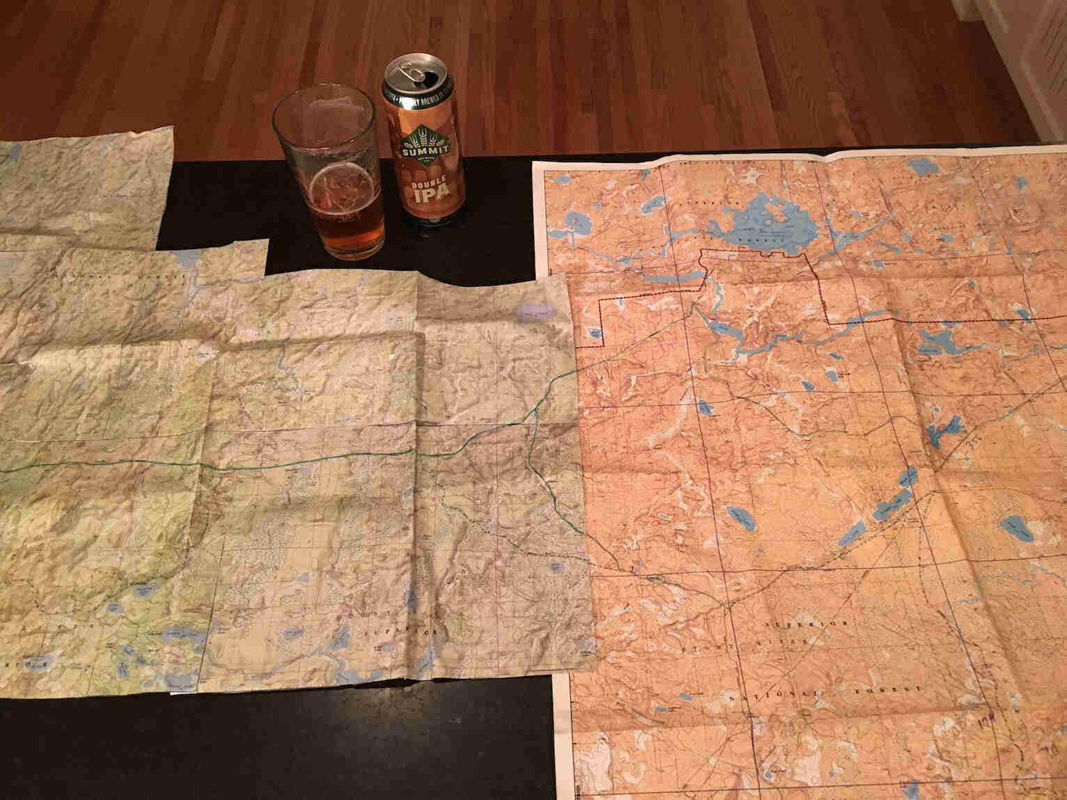 Downward view of two maps, a glass of beer and can, on a table top