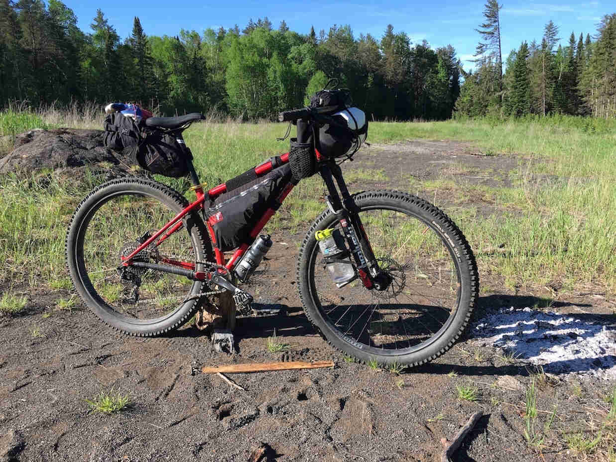 Right side view of a Surly bike, red, on a patch of red gravel in a grassy field, with trees in the background