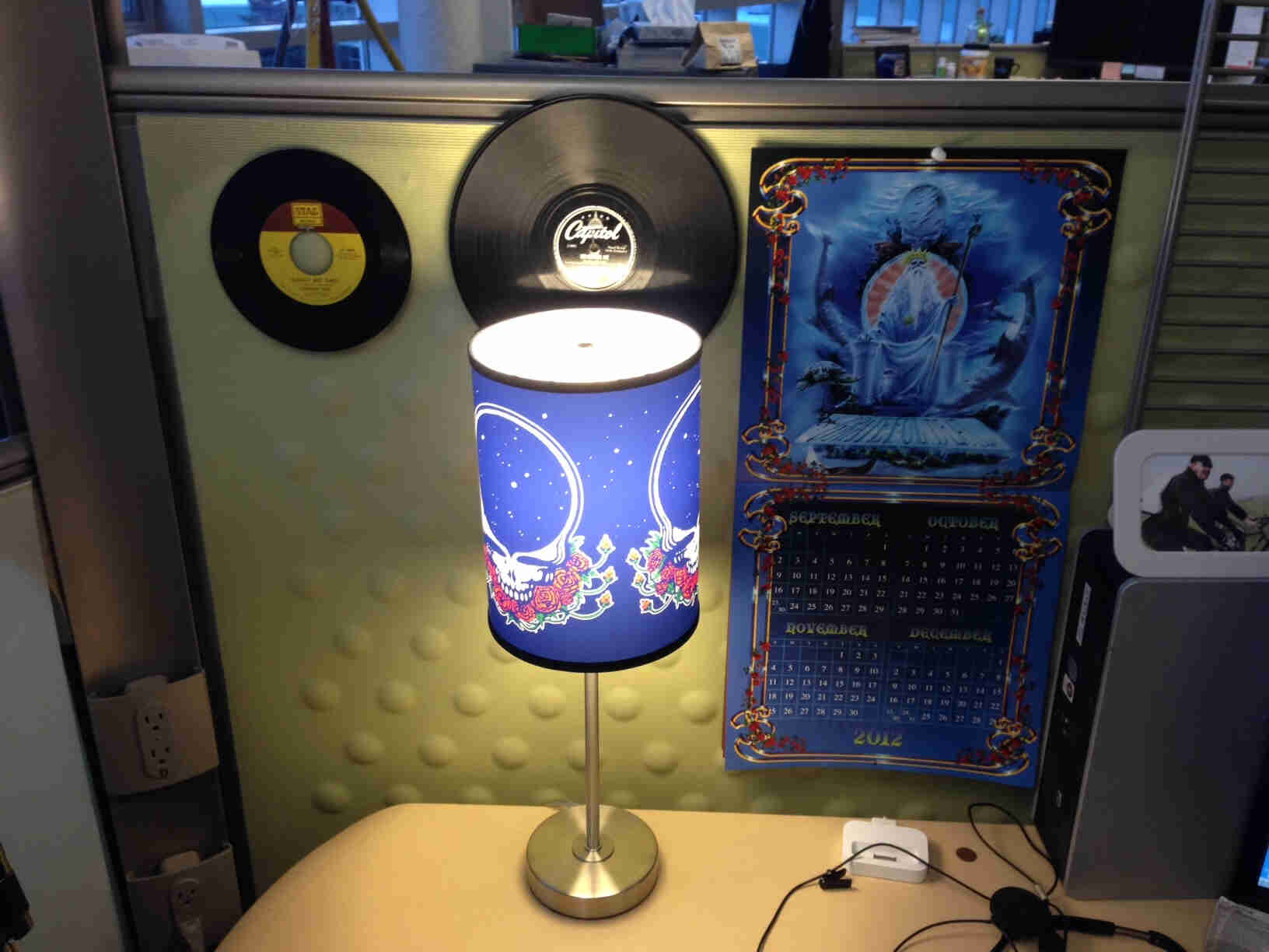 A lamp with a Grateful Dead shade, on a table in a cubicle, with records on a wall behind it