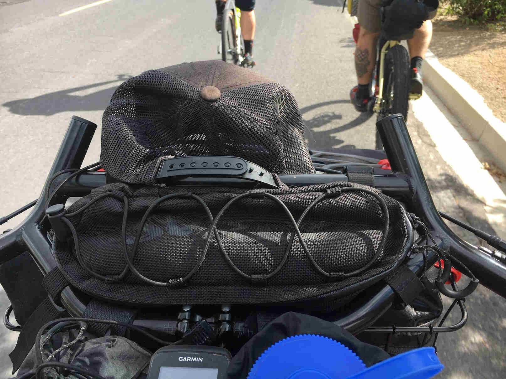 Downward close up of the handlebars loaded with gear on a bike with other cyclist in front view