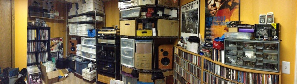 Panoramic view of an interior room, with shelves loaded with record albums and stereo equipment, against the walls
