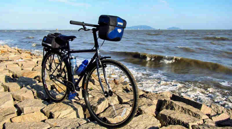 Front right side view of a black Surly Cross Check bike, parked on a rocky back of the sea