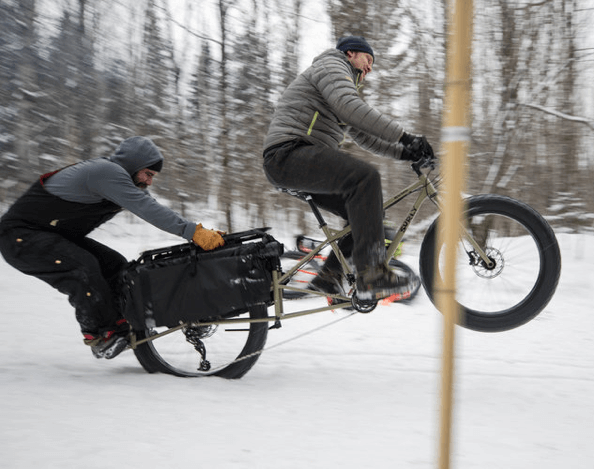 Right side view of a cyclist popping a wheelie on a Surly Big Fat Dummy bike in the snow, with a person hanging on back
