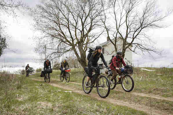 Front view of cyclists riding down an incline on a country dirt/grass road in front of a farmhouse