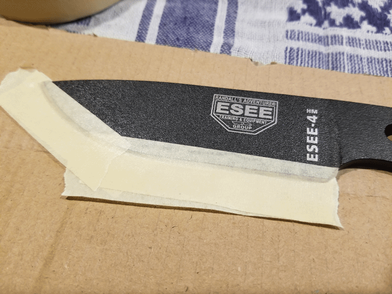 Black powder coated knife blade taped to a piece of cardboard with masking tape