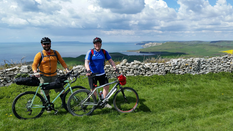 Two cyclist standing behind their bikes, right side view, with a stone wall and the sea in the background