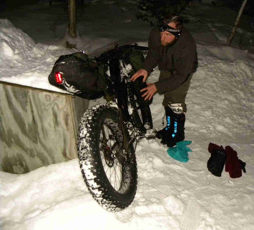 Rear, right side view of a Surly Moonlander bike, on deep snow, with person loading gear on the right side at night