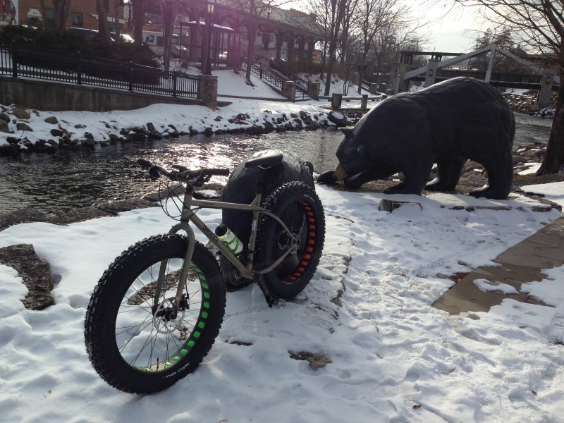 Left side view of a Surly Moonlander fat bike, parked in snow next to a stream, with a brown bear statue in background