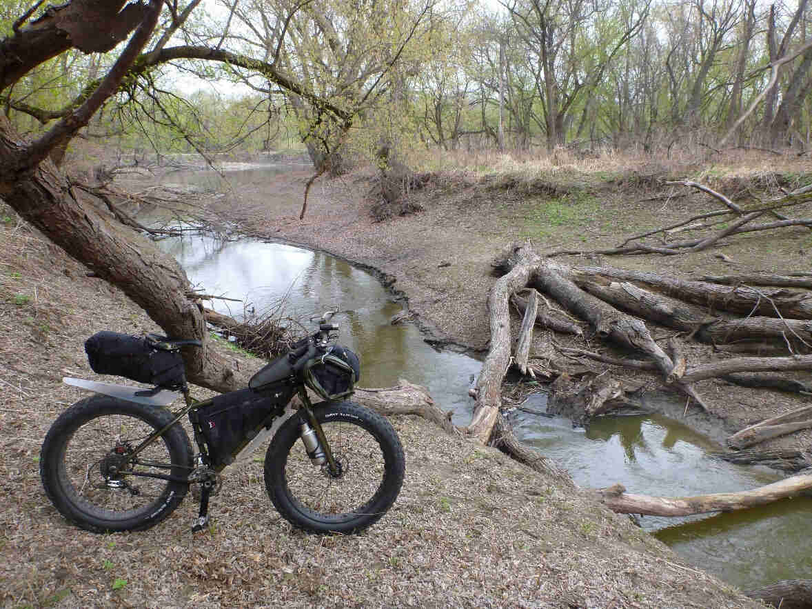 Right side view of an olive drab Surly Moonlander bike, parked on a bare bank, facing a stream with a downed tree in it