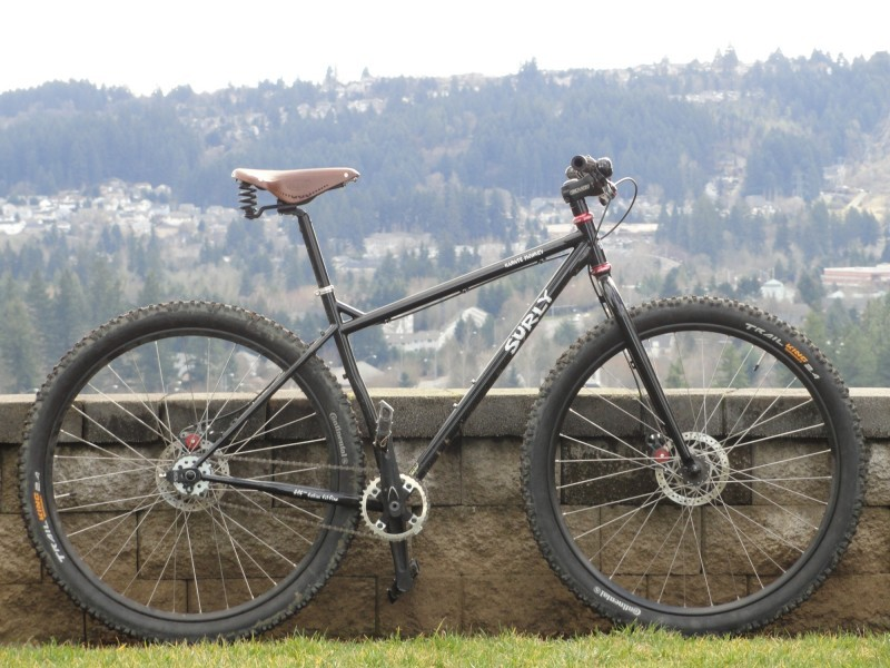 Right side view of a black Surly Karate Monkey bike, parked along a stone block wall, with a town on a hill behind it